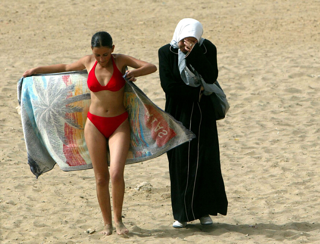 A young woman wearing a bikini walks along the beach with a friend in dressed in traditional clothes..