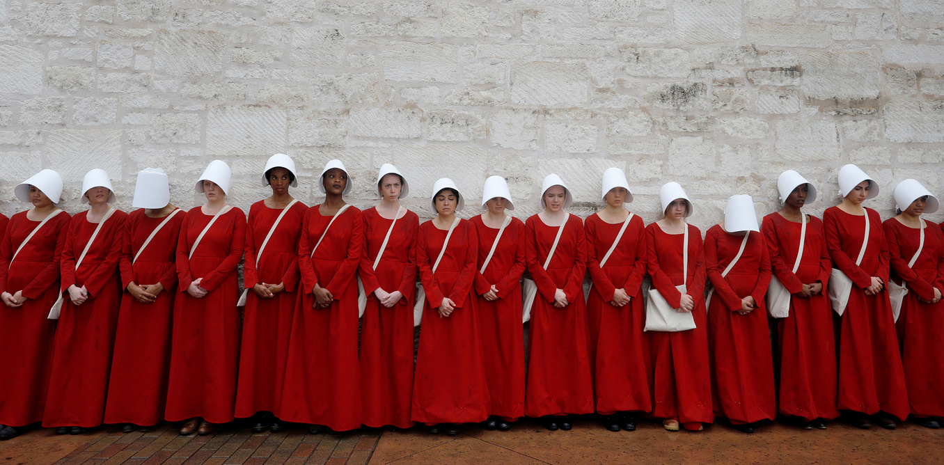 "Women dressed as handmaids promoting the Hulu original series ""The Handmaid's Tale"" stand along a public street during the South by Southwest Music Film Interactive Festival 2017 in Austin"